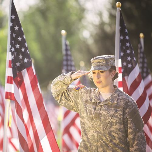 Female Solider Saluting American Flags